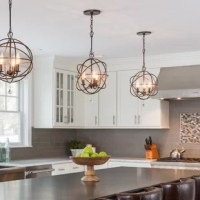 Defined by its distinctive armillary silhouette, this three-light globe chandelier brings a splash of contemporary style as it illuminates any arrangement in your home. Crafted from metal, this fixture features a round sloped-ceiling-compatible canopy, an adjustable hanging chain, and an openwork shade comprised of interlocking rings in a versatile solid finish. A trio of 60 W candelabra-base bulbs (not included) sits ensconced within to offer a boost of brightness. The manufacturer backs this...