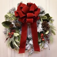 Gorgeous Winter Wreath  perfect for decorating all season long.  Created with   snow  flocked pine, variegated laurel leaves, magnolia foliage, pine cones and berries. Accented with a hand tied red velvet ribbon