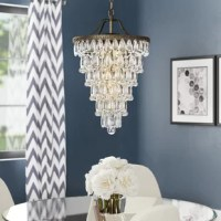 Elevate your dining room or living room ensemble with this eye-catching 4-light chandelier. Sure to grab glances and compliments, this piece features 129 teardrop-shaped glass crystals arranged in seven tiers. The round frame comes crafted from iron and accented with subtle scrolling engraved details. Inside the frame are four iron sockets which accommodate one 60W candelabra bulb (not included). This chandelier is suspended with a chain with an adjustable height ranging from 2