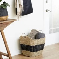 This Contemporary style large wicker basket is handwoven from natural beige flatsedge wicker, a natural Vietnamese seagrass with a smooth texture. The wicker rope is braided into horizontal bands to form the firm, non-collapsible body, creating a durable, large basket for heavy items. The unique rounded rectangular shape boasts tall sides, a curved silhouette, a black stripe, and chic circular metal handles. This decorative basket offers both a neutral-toned decorative basket in Coastal spaces...
