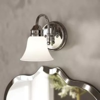 Bring some enhancing illumination to your bathroom or powder room walls with this 1-light bath sconce. A classic silhouette, this sconce offers a simple contemporary-inspired style. A round steel backplate supports a curved arm and bell-shaped white glass shade. This hardwired luminary accommodates one medium-base A19 lightbulb of up to 100 W (not included). It is compatible with dimmer kits. It can be installed so that the light direction can face either up or down, based on your needs.