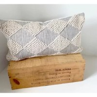 Handwoven in India, this pillow brings beauty and texture to any room. It has a raised diamond design on a textured grey ground. The item has a zipper closure and a designer quality feather and down insert.