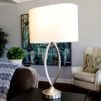 Add a sculptural element to your side table with Latitude Run Table Lamp. This sleek, modern crafted lamp features an open design for a look with will keep your side table looking open and airy. A classic finish is accented by a White Linen Oval hardback shade.