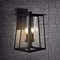 Dramatic and sleek, this contemporary outdoor wall lantern brings instant style to any home exterior. Designed with chic clear glass and a finely crafted minimalist black metal frame, its elegant interior candelabra makes it a luxurious modern classic.