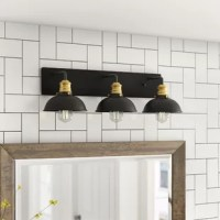 Create an industrial vintage look in your warehouse-inspired space with this striking three-light armed sconce. The wall sconce features three black bell-shaped shades with a black and brass finish. A metal arm connects each light to a sleek, black metal panel, providing an eye-catching contrast to the concentric brass detailing. Perfect for your kitchen, bedroom, bathroom, study, or hallway, this 8.3'' H x 27'' W hardwired fixture adds a just-right modern touch.