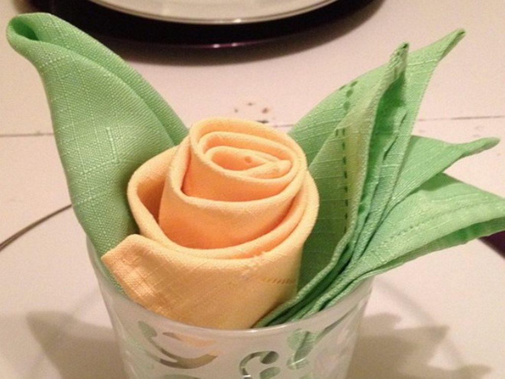 एक गिलास में नैपकिन से गुलाब