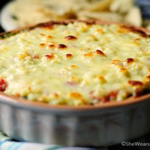 This Warm Layered Black Bean Dip with cilantro pesto and Monterey Jack cheese is a delicious addition to any gathering.