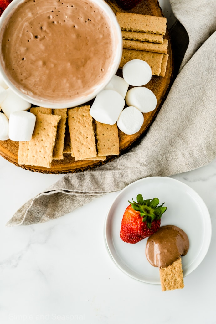 dipped strawberry and graham cracker on a plate