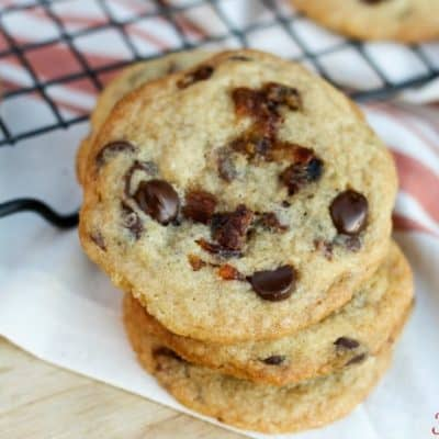 stack of baked candied bacon chocolate chip cookies with cooling rack in background