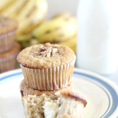 three muffins on a plate with bananas and milk in the background