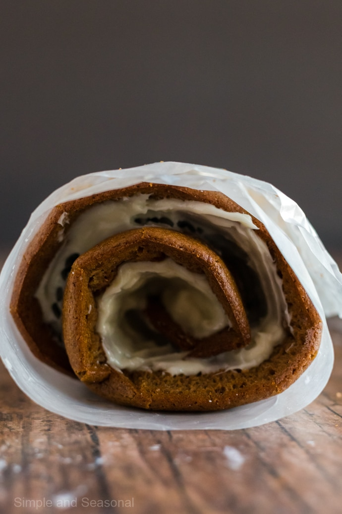 side view of pumpkin roll after filling with frosting and rolling up again