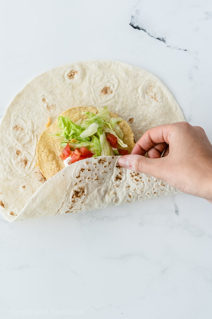 folding process to wrap large tortilla around crunchy shell in the center