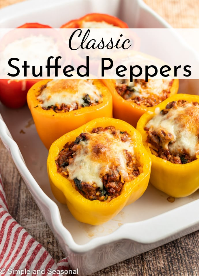 yellow and red stuffed peppers in a white baking pan