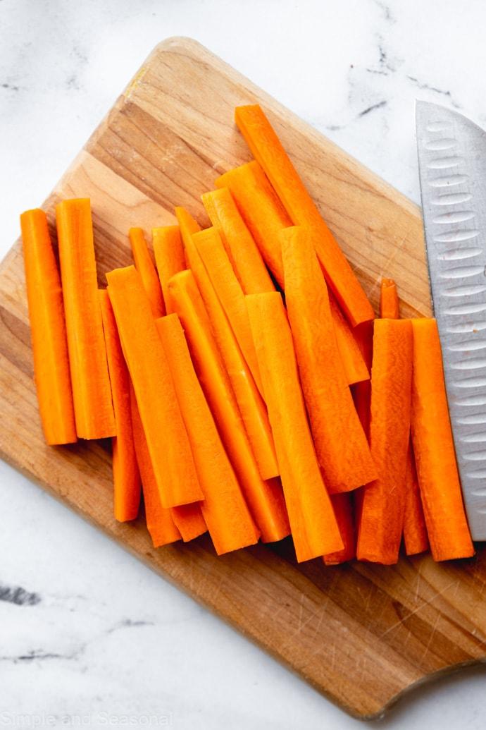 carrots cut into sticks on a cutting board