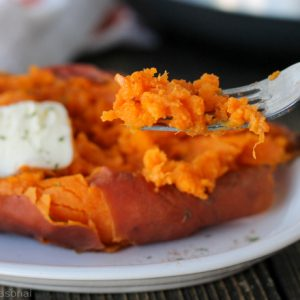 sweet potato on a fork with a cooked potato in the background