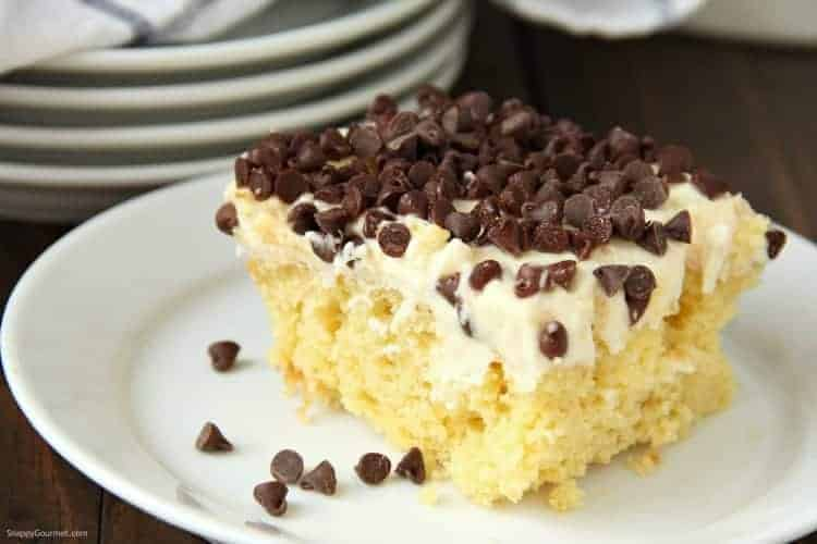 Cannoli Poke Cake on plate with chocolate chips
