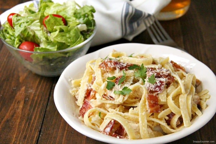 cheesy Chicken Bacon Alfredo Pasta in bowl with salad and napkin