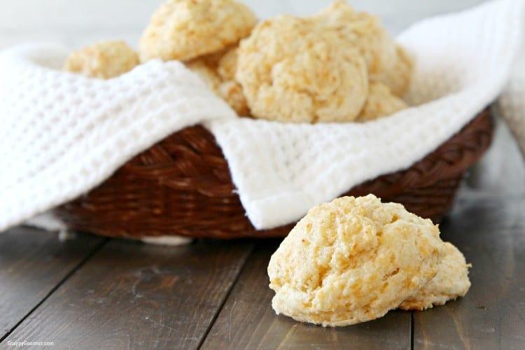 stacked garlic cheddar drop biscuits next to bread basket