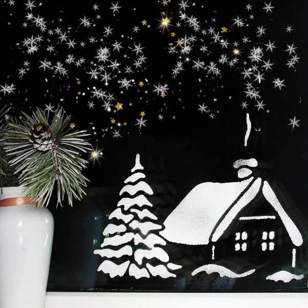 Snow covered house New Year's drawing made of flour on a photo window