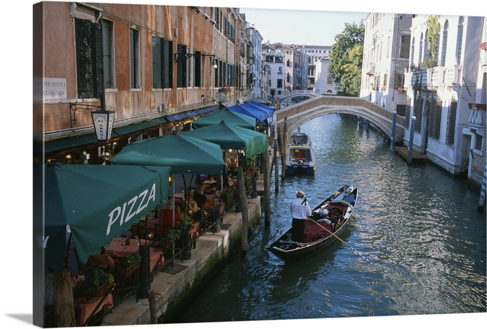 A gondolier passes a restaurant on a canal in Venice ...