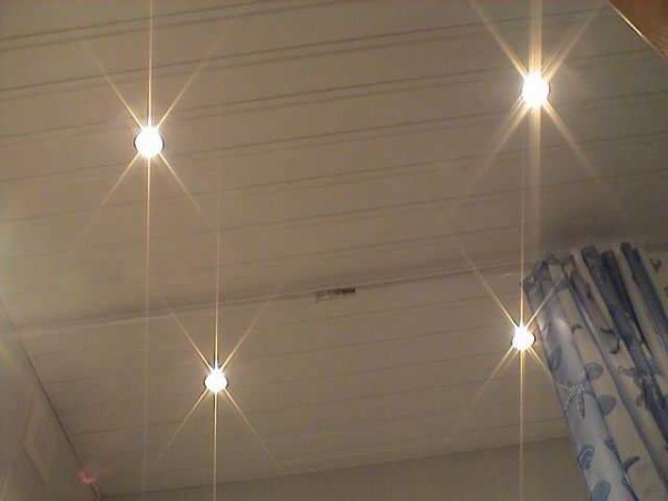 Quattro lampadine alogene sul soffitto di plastica sono alimentate da un trasformatore