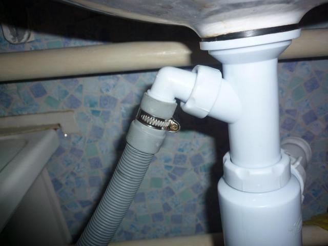 Шланг посудомоечной машины, подсоединенный к патрубкукухонного сифона.