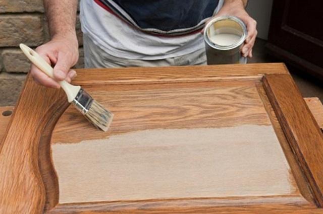 Нанесение лака на деревянную панель.