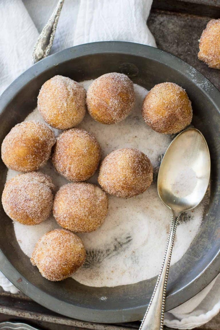 Easy no-yeast donut holes filled with a sweet cream cheese frosting and rolled in cinnamon-sugar.