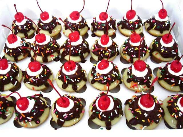 Fluffy vanilla cupcakes topped with chocolate frosting, a fudge drizzle, sweet swirls of vanilla buttercream, sprinkles and a cherry on top!