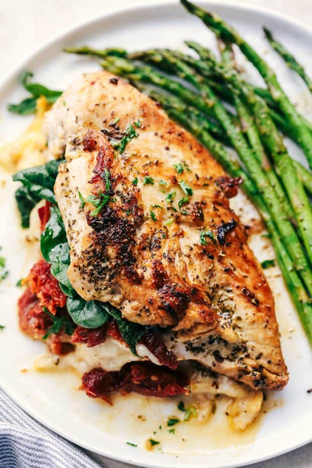 Stuffed Tuscan Garlic Chickenare tender and juicy chicken stuffed with mozzarella cheese, sun-dried tomatoes, and spinach that gets baked in a creamy garlic sauce.This meal will blow the family away!