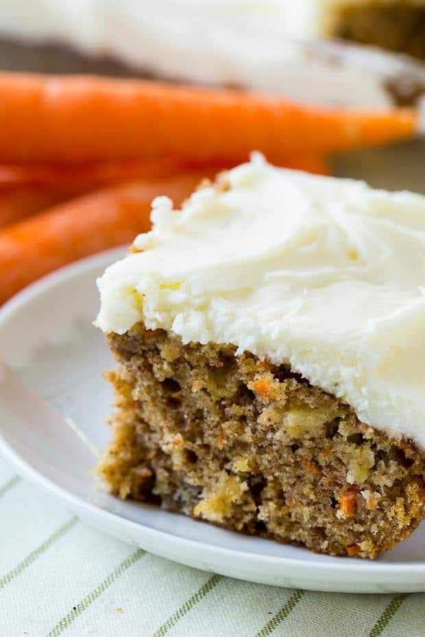 Pineapple Carrot Cake is super moist and has lots of spice flavor. Made in a 9X13-inch pan, it's easy to cut into squares and share. The cake is covered in a rich and creamy cream cheese icing.