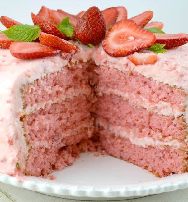 Our Easy Strawberry Triple Decker Cake Recipe is an absolute showstopper. Loaded with Fresh Strawberries, this Homemade Southern Delight is guarentted to be a hit! Super Moist, Rich and Really Sweet, all topped with Strawberry Buttercream Frosting!!