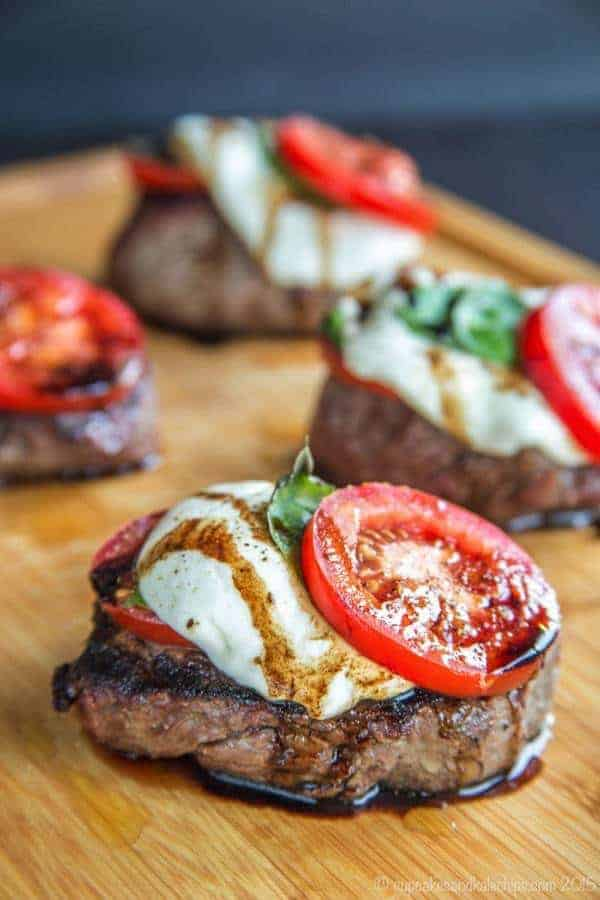 Caprese Grilled Filet Mignon is a simple way to dress up some amazing Certified Angus Beef brand filets with some of the freshest ingredients of summer. After simply seasoned with salt and pepper and grilling filet mignon, it is then topped with juicy tomatoes, fresh mozzarella, basil, and a balsamic reduction for an easy dinner recipe that is also a little extra special. This filet mignon recipe is not only delicious, it is also naturally gluten free and low carb.
