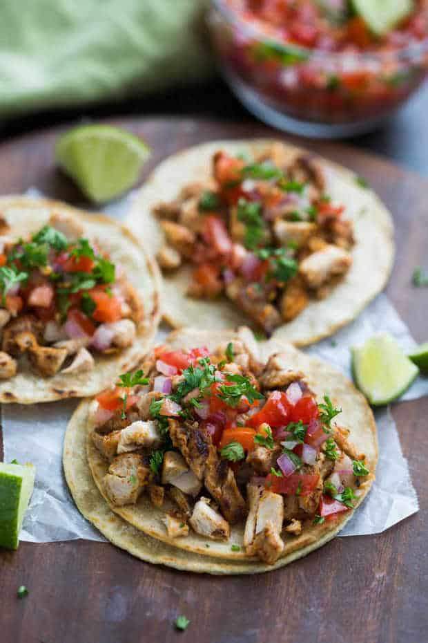 My family goes crazy for these grilled chicken tacos, and I love how EASY they are to make! Marinated chicken thighs are grilled to perfection and served with warmed corn tortillas, pico de gallo, and cilantro.