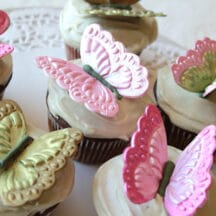 molded gumpaste butterflies in pink and green, on top of white frosting topped cupcakes