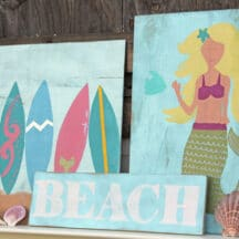 """multiple beach themed signs stacked against one another - surfboards, """"BEACH"""", mermaid, and seashells"""