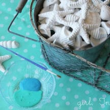 bucket of plaster of paris seashells, blue paint, on blue polka dot tablecloth