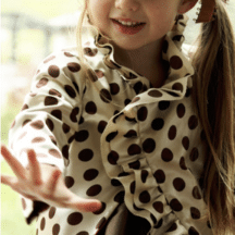 front view of white and brown polka dot jacket on lilttle girl