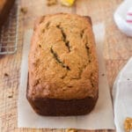 banana nut bread loaf next to cooling rack, with banana peel and tea towel