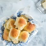 dinner rolls stacked in a bread basket with white and blue floral linen, baking dish with rolls and butter on a dish