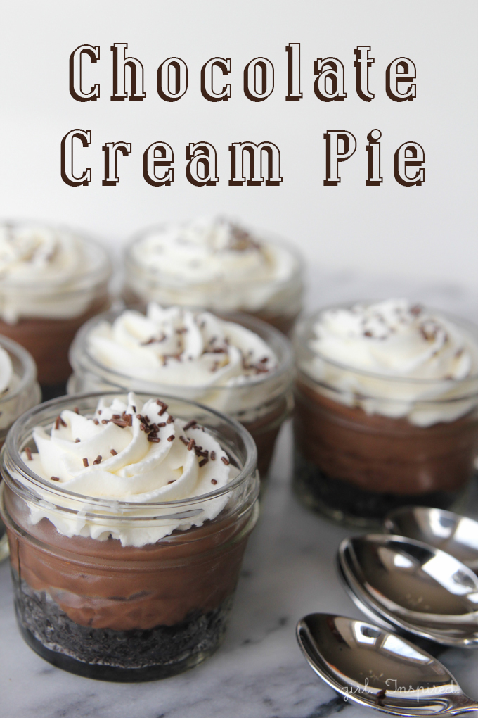 Chocolate crust, chocolate custard, and whipped cream layered in small mason jars with silver spoons and a text overlay.