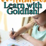 girl with blue crayon writing numbers on worksheet counting goldfish crackers with text overlay