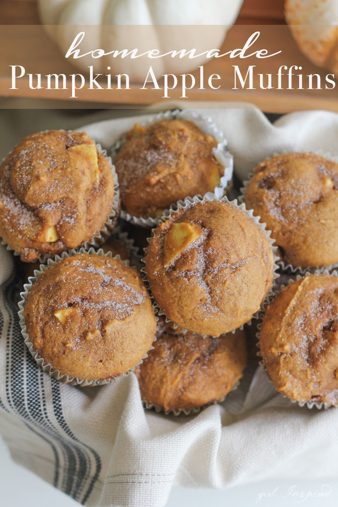 pumpkin apple muffins stacked on a white and blue striped linen, with pumpkins in the background.