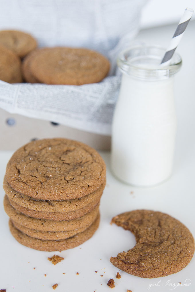 Ginger cookies stacked in newsprint-lined tin, cookies and jar of milk on white table in front of tin