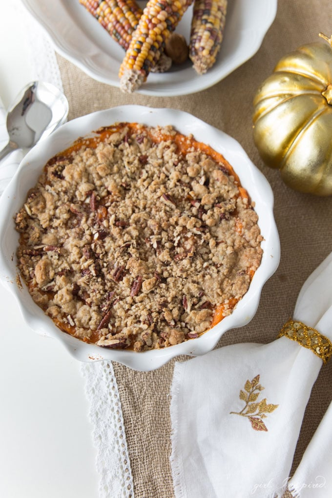 Mashed yams topped with brown sugar and pecan streusel in a white pie plate with gold pumpkin, table linens, and decorative corn on tabletop.