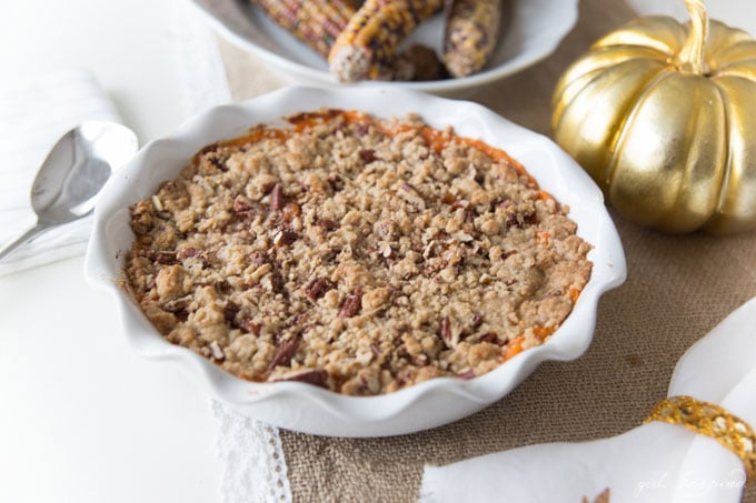 Mashed yams topped with brown sugar and pecan streusel in a white pie plate and table decorations.