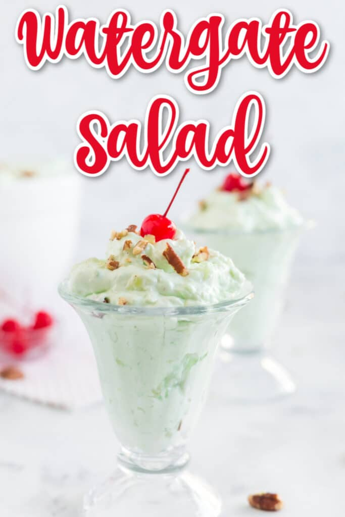 Watergate Salad in glass ice cream dishes with three maraschino cherries and pecans on top with text overlay