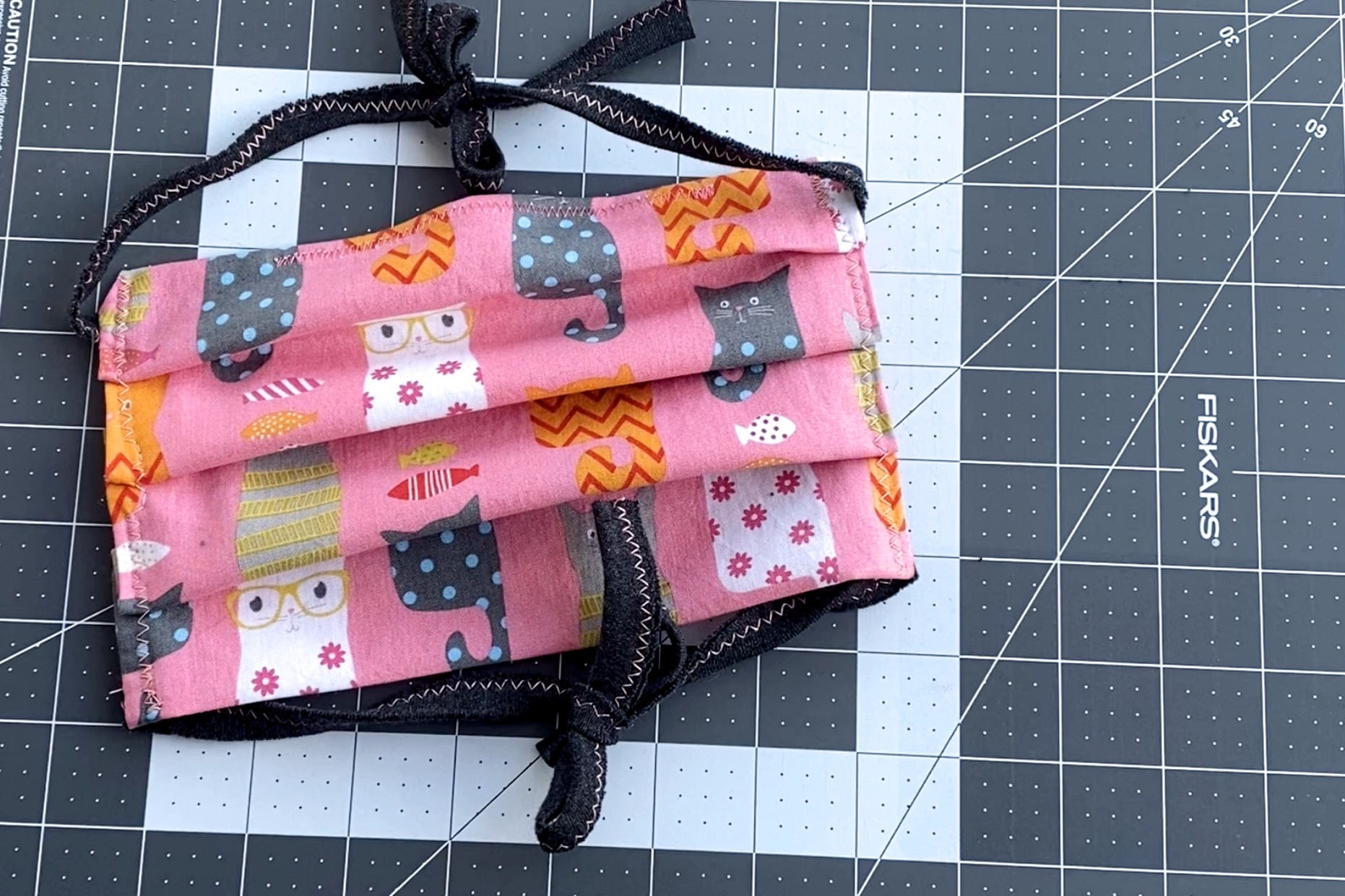 Cat Pattern on pink face mask on grey and white sewing cut mat