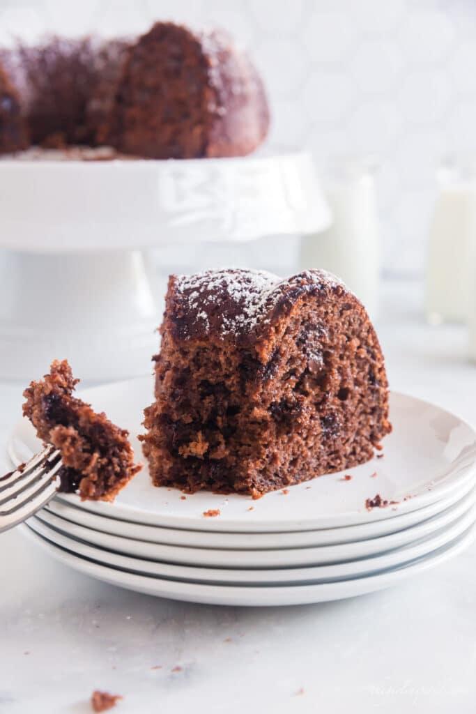 bite of cake on fork next to Kahlua cake slice on stack of white plates, white cake platter and jars of milk in background