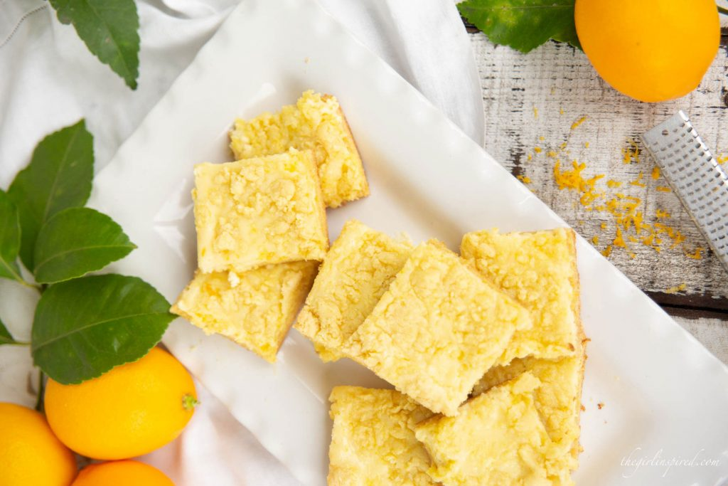 lemon crumble square cookies on white plate with whole lemons arranged around plate